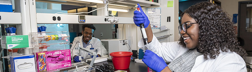 Photo of two students in a lab